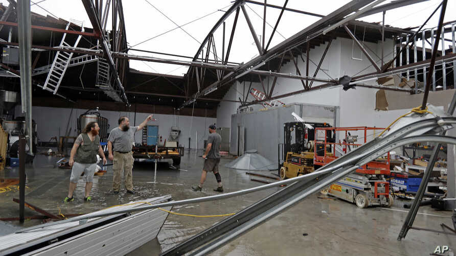 Ethan Hall, right, Michael Jenkins, center, and Nash Fralick, left, examine damage to Tidewater Brewing Co. in Wilmington, N.C., after Hurricane Florence made landfall, Sept. 14, 2018.