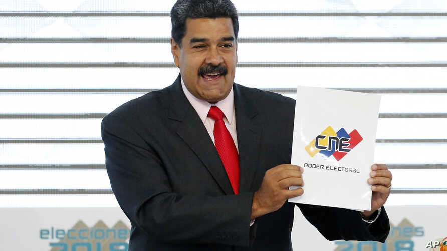 FILE - Venezuela's President Nicolas Maduro holds up the National Electoral Council certificate declaring him the winner of the presidential election, during a ceremony at CNE headquarters in Caracas, Venezuela, May 22, 2018. As a meeting last August...