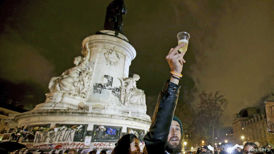 """A man holds a glass of champaign on the """"Republique"""" square, a week after a series of deadly attacks in the French capital, in Paris, France, Nov. 20, 2015."""