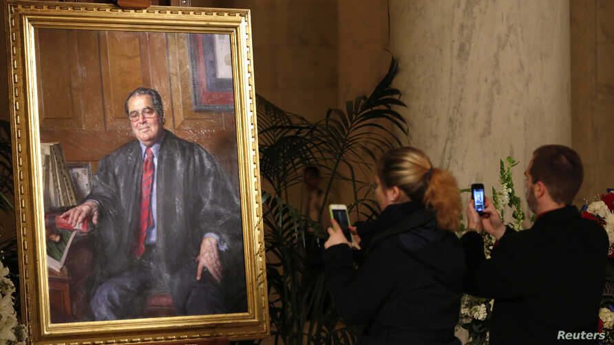 A couple takes photographs of a painting of late U.S. Supreme Court Justice Antonin Scalia in the Great Hall of the Supreme Court in Washington, Feb. 19, 2016.