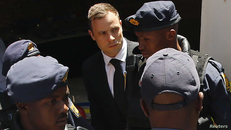 South African Olympic and Paralympic sprinter Oscar Pistorius (C) is escorted to a police van after his sentencing at the North Gauteng High Court in Pretoria, Oct. 21, 2014.