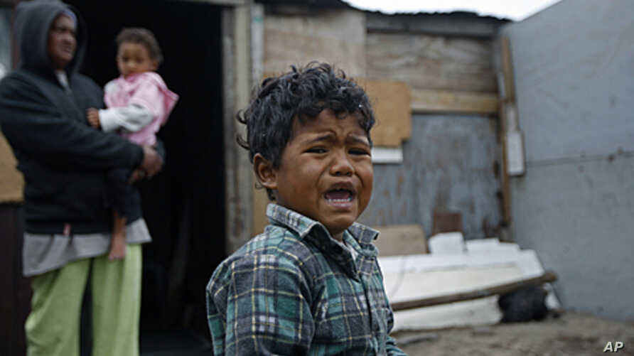 A boy reacts, in front of a house in a township on the outskirts of Cape Town, South Africa. Thousands of South Africans live without running water in their houses and without electricity. (2010 file photo)