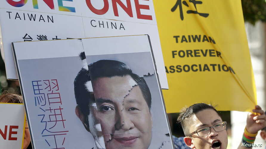 aAn activist holding a placard showing the merged faces of Taiwan's President Ma Ying-jeou and China's President Xi Jinping, protests against the upcoming Singapore meeting between Ma and Xi, in front of the Presidential Office in Taipei, Taiwan, Nov