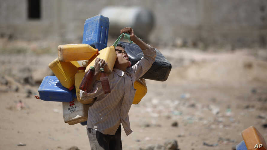 A boy carries buckets to fill with water from a public tap amid an acute shortage of water, on the outskirts of Sanaa, Yemen, Tuesday, Oct. 13, 2015.