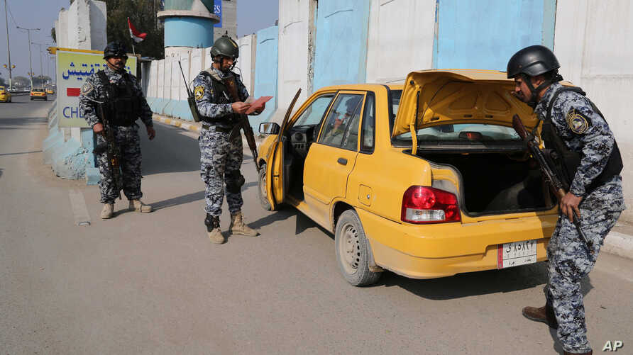 FILE - Iraqi federal policemen search a car at a checkpoint in Baghdad, Iraq, Thursday, Jan. 23, 2014.