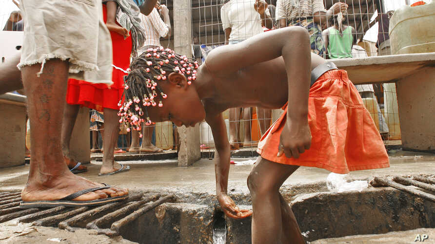 FILE - An Angolan child washes in a ditch near a water pump in Luanda.