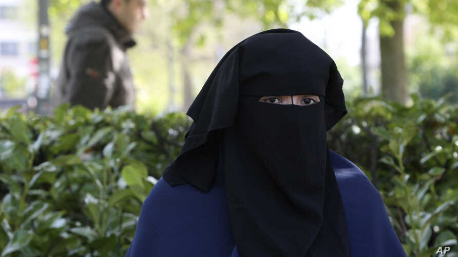 FILE - Selma, a 22 year old woman, wears the niqab as she sits in a park in Brussels, April 22, 2010.