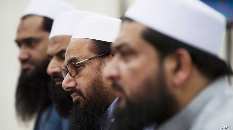 FILE - Hafiz Saeed, second from right, chief of Pakistani religious group Jamaat-ud-Dawa listens to reporters at a news conference in Islamabad, Pakistan, Nov. 2, 2015.
