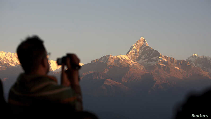 FILE - Tourists take pictures at Sarangkot in Pokhara, with the view of the Mount Annapurna range in the background, some 200 km (124 miles) west of Kathmandu, Nov. 30, 2008. Annapurna, at 8,091meters high, is the tenth highest mountain in the world.