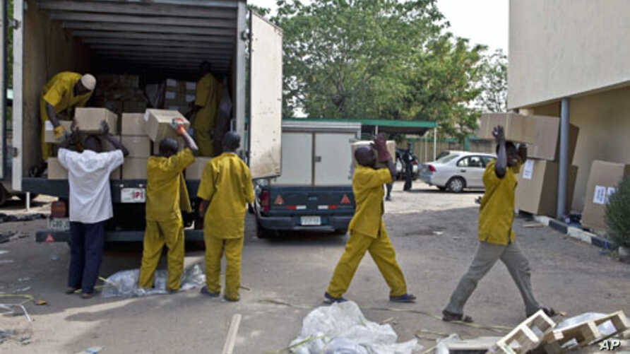 Electoral officers unload election materials from a vehicle at the Independent National Electoral Commission building in northern city of Kano, Nigeria, April 3, 2011