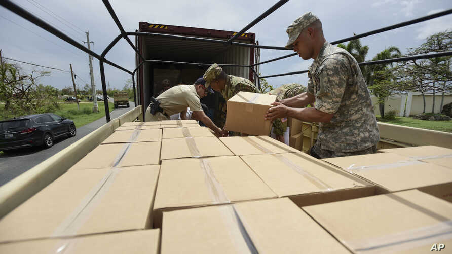 FILE - Soldiers and National Guard members organize aid in the aftermath of Hurricane Maria in Guayama, Puerto Rico, Oct. 5, 2017.