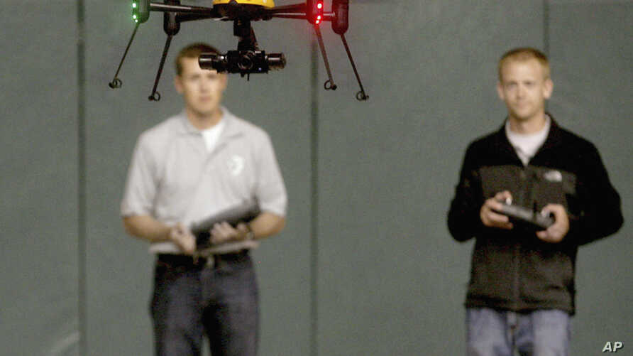 FILE - Students at John D. Odegard School of Aerospace Sciences at the University of North Dakota in Grand Forks, North Dakota, remotely pilot a drone during a demonstration, in a June 24, 2014, photo.
