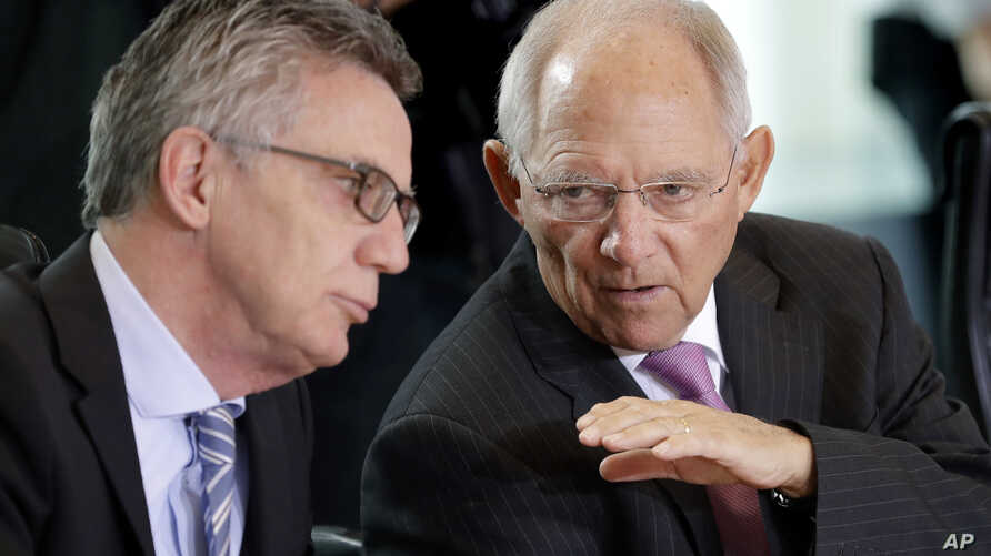 German Interior Minister Thomas de Maiziere, left, and German Finance Minister Wolfgang Schaeuble, right, talk prior to the weekly cabinet meeting at the chancellery in Berlin, Germany, Wednesday, April 5, 2017.