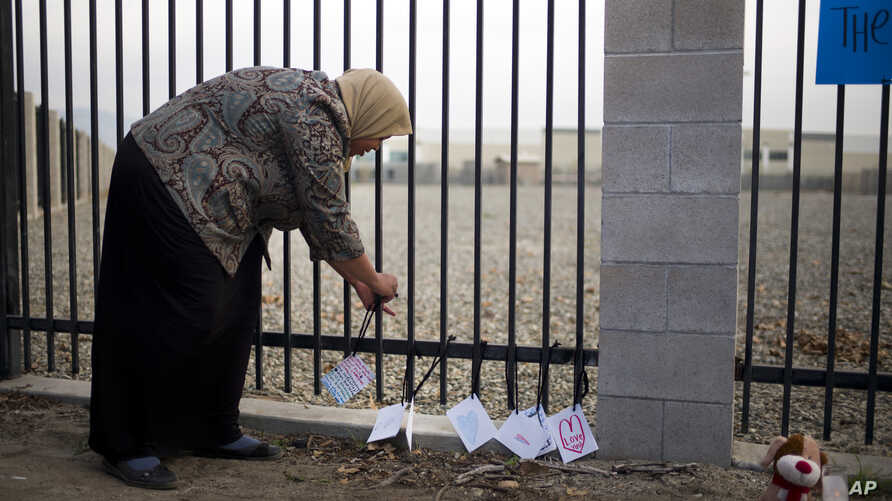 Kareema Abdul-Khabir, who teaches special needs students at an elementary school in Barstow, Calif., places some cards made by her students at a makeshift memorial honoring the victims of Wednesday's shooting rampage in San Bernardino, Dec. 4, 2015.