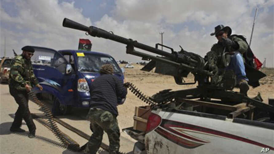 A Libyan rebel, dressed as a cowboy,  mans an anti-aircraft gun as fellow rebels load ammunition as they wait for the signal to advance at an intersection just outside Brega, Libya, Sunday, April 3, 2011. Libyan rebels want to install a parliamentary
