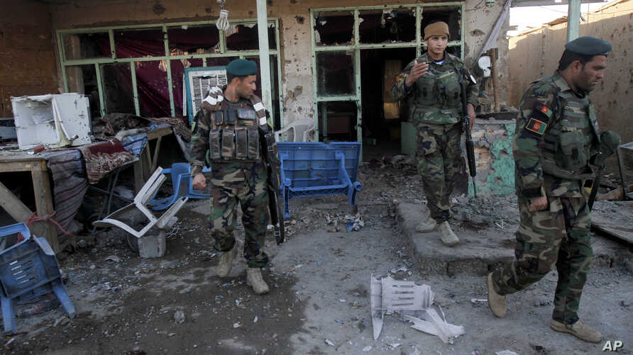 Afghan security forces inspect damages after clashes between Taliban fighters and Afghan forces in Kandahar Airfield, Afghanistan, Wednesday, Dec. 9, 2015.