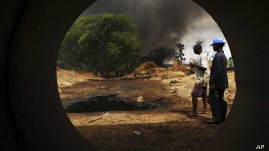 Workers, seen through a pipe, look on at the scene of an oil pipeline fire in Dadabili, Niger state. (File)