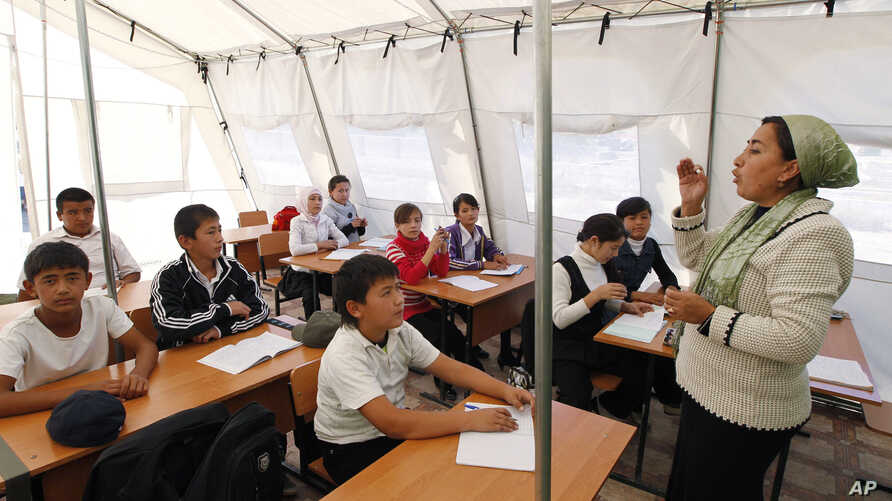 FILE - Children listen to their teacher during a lesson at a local school, based in a tent, in the city of Osh, Kyrgyzstan.