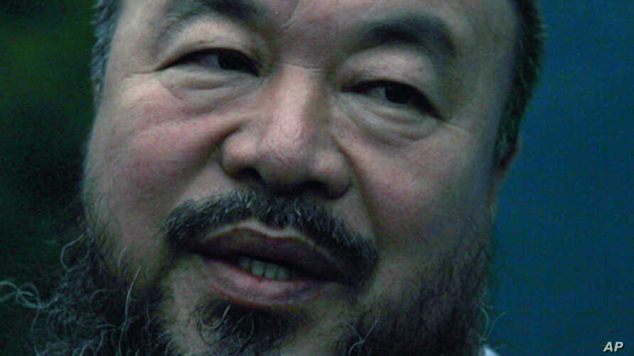 Dissident Chinese artist Ai Weiwei speaks to members of the media in the doorway of his studio after he was released on bail in Beijing, June 23, 2011.