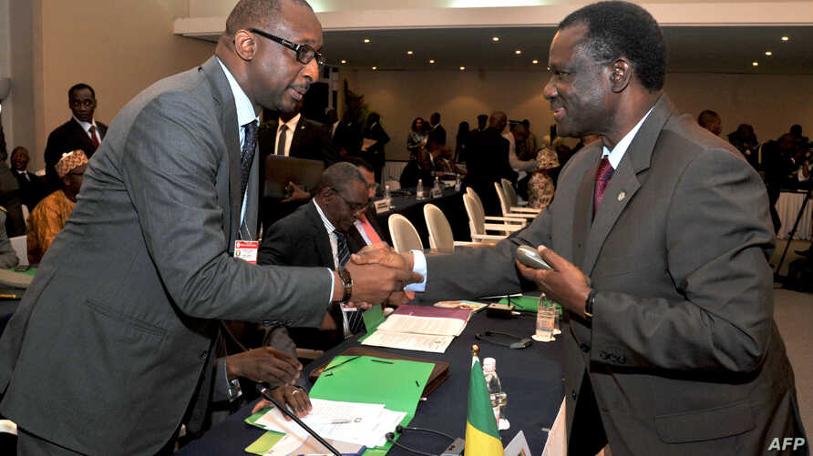 President of ECOWAS) Desire Kadre Ouedraogo (R), greets Malian Foreign Minister Tieman Coulibaly on Sept. 17, 2012 in Abidjan