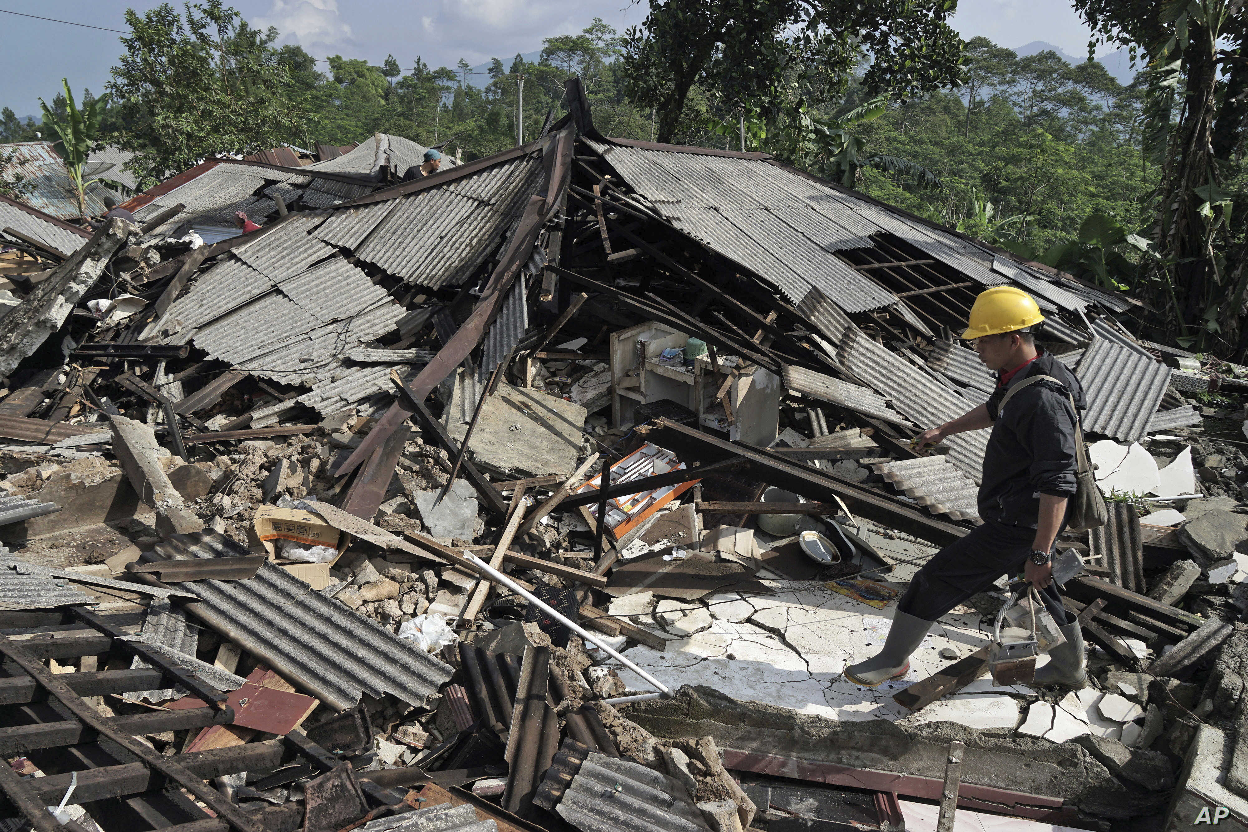 A rescuer walks on the rubble of houses in an area affected by an earthquake in Kalibening, Central Java, Indonesia, April 19, 2018.