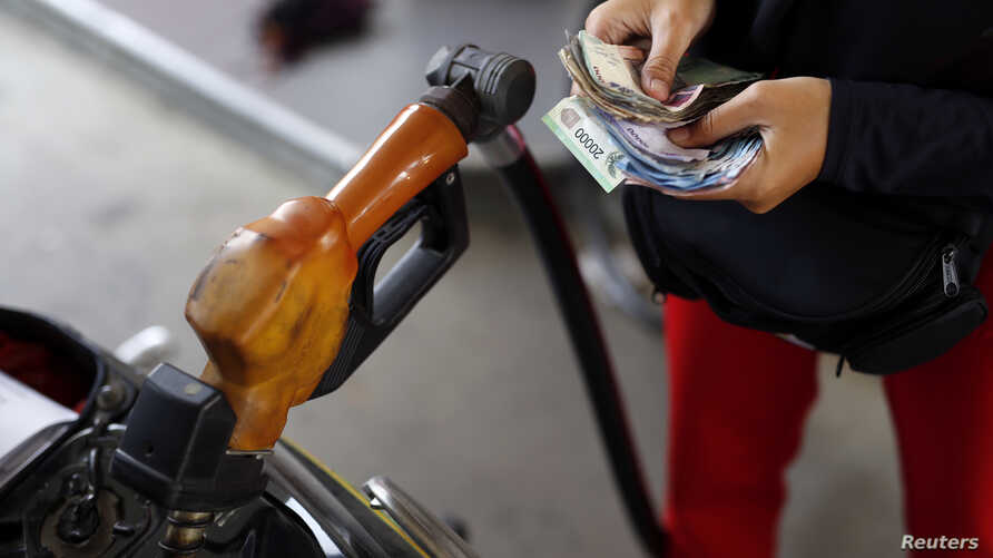 FILE - A worker at a state-owned Pertamina petrol station holds money as a motorcycle is filled with subsidised fuel in Jakarta, Oct. 31, 2014.