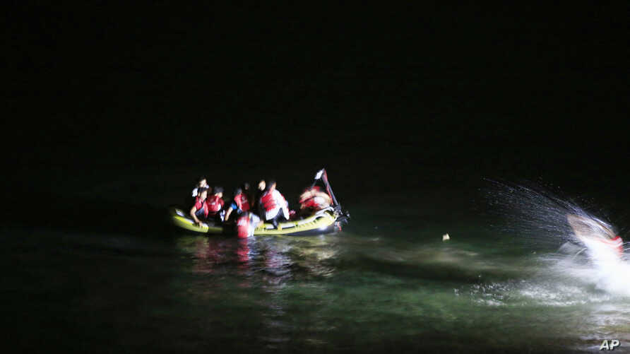 Migrants on board a dinghy try to cross to the nearby Greek island of Kos, from the coastal town of Bodrum, Turkey, early Friday, Aug. 14, 2015.