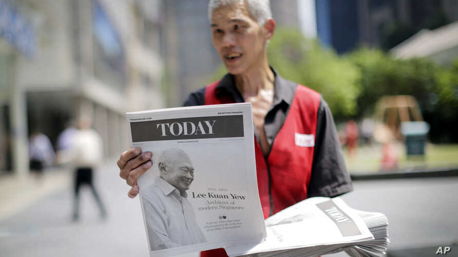 A vendor hands out a special edition of a local newspaper featuring the life of the late Lee Kuan Yew, during lunch hour in the financial district, Monday, March 23, 2015, in Singapore. Singaporeans wept and world leaders paid tribute Monday as the S...