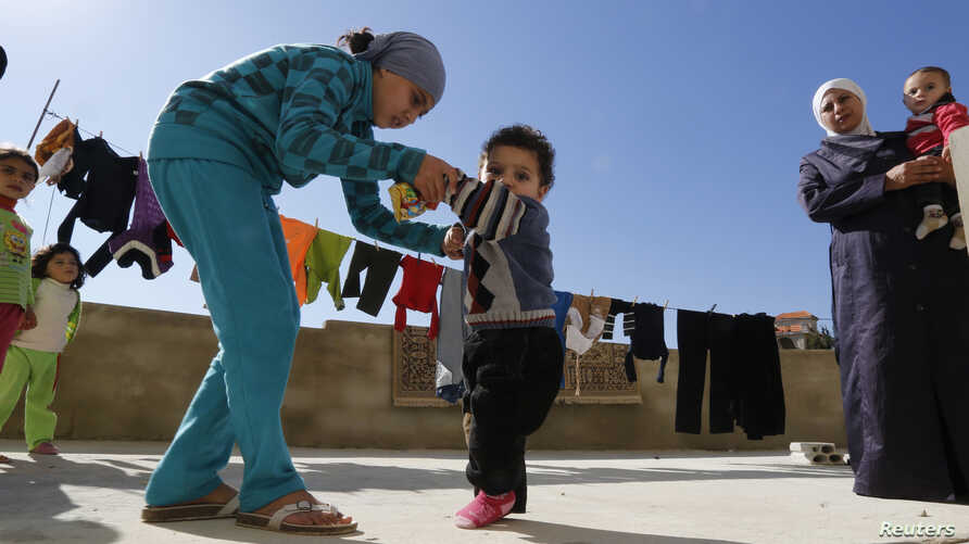 A Syrian refugee girl helps her brother, who the family suspects has polio, to walk as their mother watches, in a mosque compound in the Shebaa area, southern Lebanon, Oct. 28, 2018.