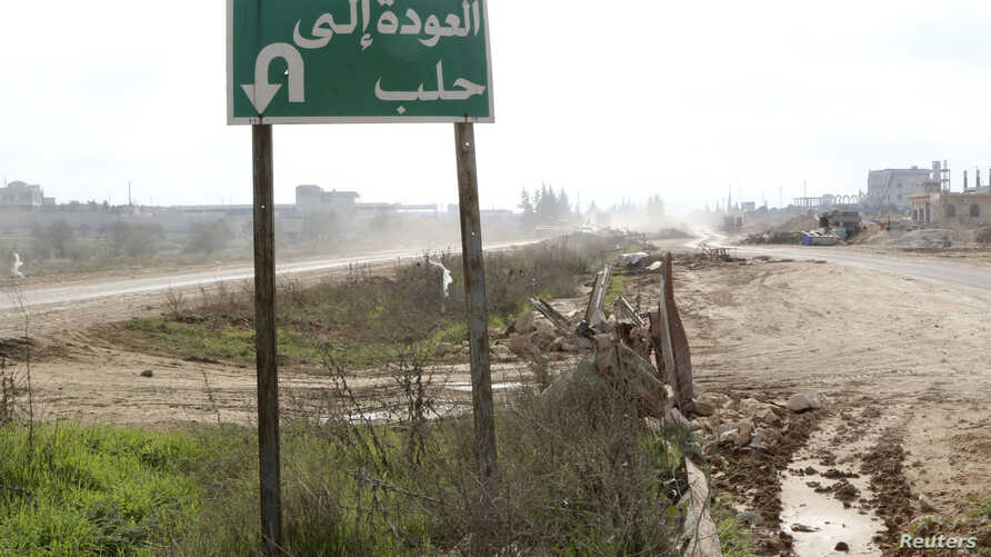 A road sign that reads 'back to Aleppo' is seen at the main north-south highway linking Aleppo with Damascus, near the Wadi al-Deif military base that the rebel fighters took control of from forces loyal to Syria's President Bashar al-Assad earlier t