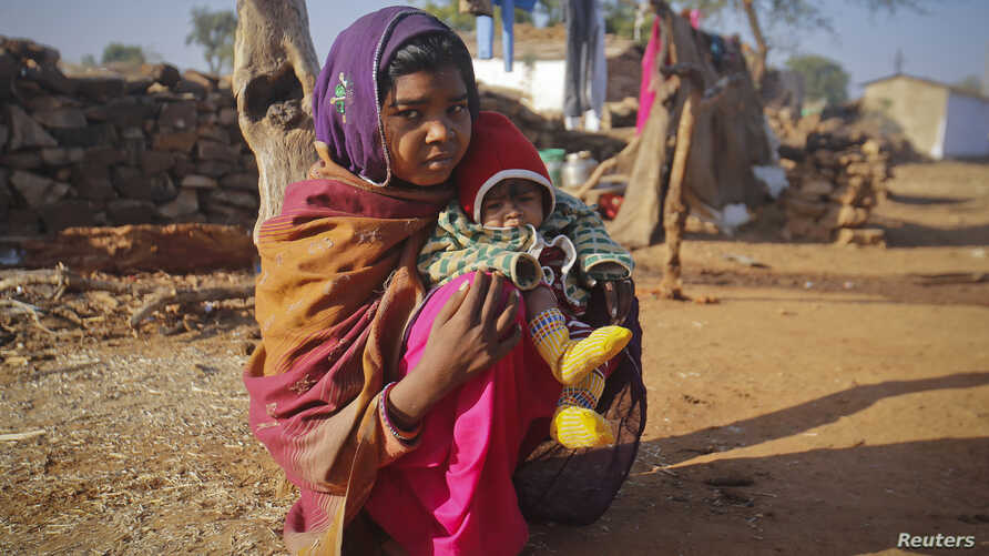 FILE - A 14-year-old girl sits with her four-month-old baby in a village in the northwestern India, January 21, 2013. The girl married her husband when she was 11 and he was 13.