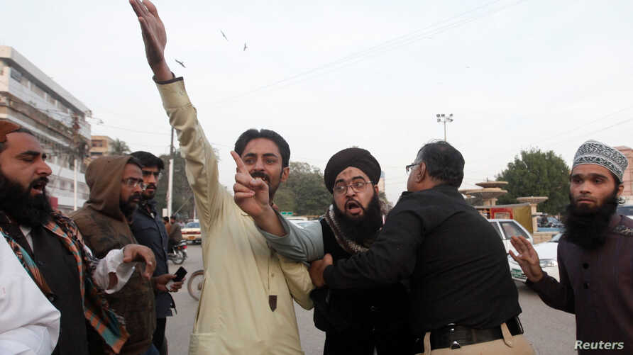 FILE - A policeman intervenes as supporters of the Tehreek Labbaik Ya Rasool Allah religious group chant slogans during a protest against human rights activists demonstrating to condemn the disappearances of social activists in Karachi, Pakistan, Jan