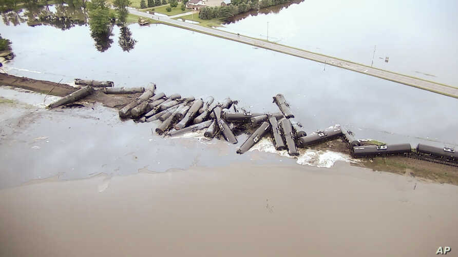 In this aerial drone image taken from video and provided by the Sioux County Sheriff's Office, tanker cars carrying crude oil are shown derailed about a mile south of Doon, Iowa, Friday, June 22, 2018.