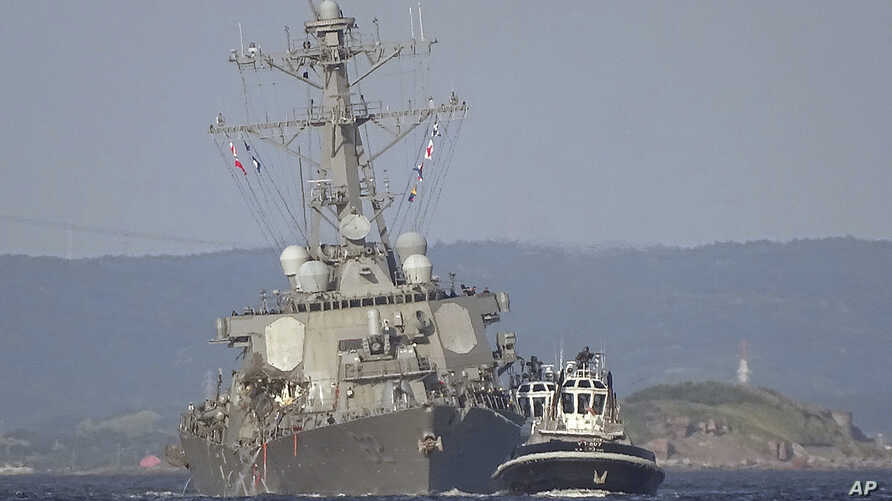 The damaged USS Fitzgerald is towed by a tugboat near the U.S. naval base in Yokosuka, southwest of Tokyo, after the destroyer collided with the Philippine-registered container ship ACX Crystal off the Izu Peninsula, June 17, 2017.