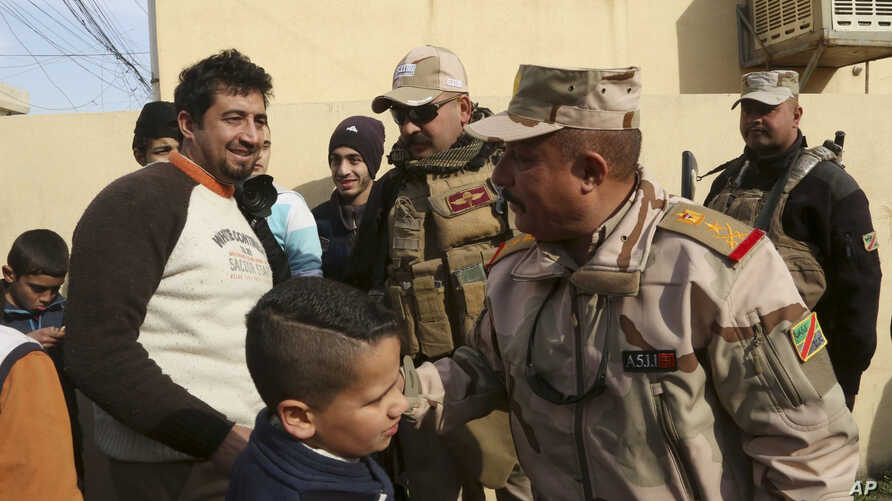 Civilians congratulate Lt. Gen. Riyadh Jalal Tawfiq, second from right, Iraqi ground forces commander as security forces patrol in the eastern side of Mosul, Iraq,  Jan. 18, 2017.