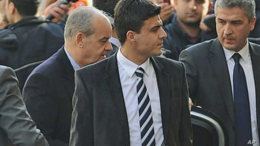 Turkey's former Chief of Staff General Ilker Basbug, center left, is surrounded by security officials as he arrives at a prosecutor's office in Istanbul, Turkey, January 5, 2012.