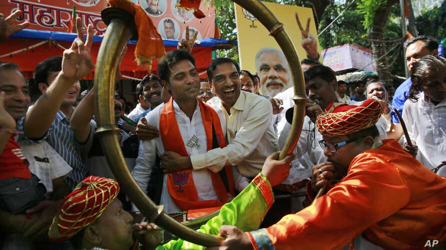 Supporters of India's ruling Bharatiya Janata Party (BJP) celebrate as early results indicated the party leading in the Maharashtra state Assembly elections in Mumbai, India, Oct. 19, 2014.