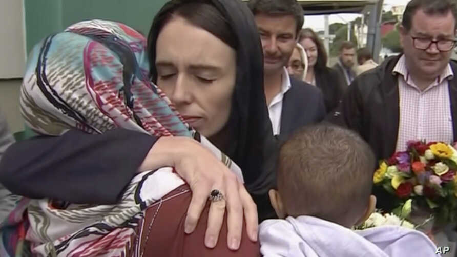 In this image made from video, New Zealand's Prime Minister Jacinda Ardern, center, hugs and consoles a woman as she visited Kilbirnie Mosque to lay flowers among tributes to Christchurch attack victims, in Wellington, March 17, 2019.