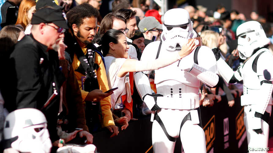 """FILE - A fan takes a selfie with a Stormtrooper at the premiere for the movie """"Solo: A Star Wars Story"""" in Los Angeles, California, U.S., May 10, 2018."""