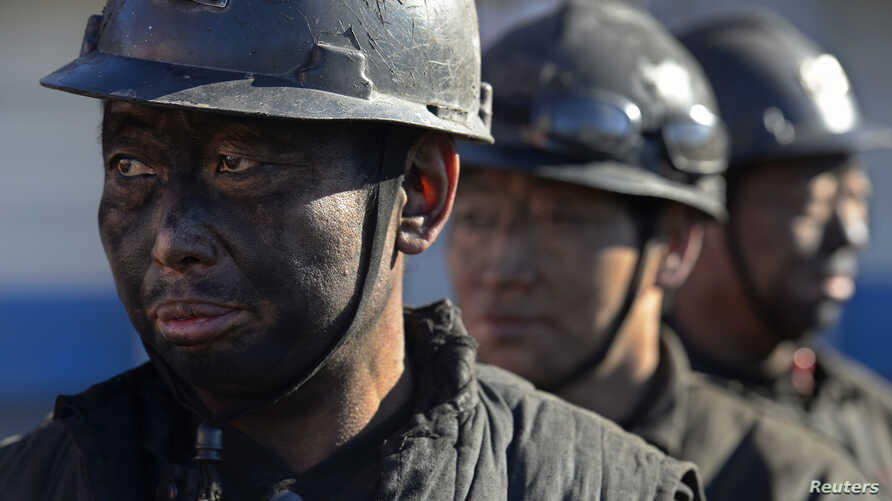 FILE - Miners wait in lines to shower during a break near a coal mine in Heshun county, Shanxi province, Dec. 5, 2014.