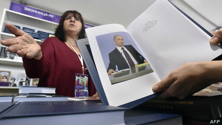 "A customer holds a copy of Russian President Vladimir Putin's book ""Direct speech"" as she speaks with a vendor (L) at the Red Square Book Festival in Moscow on June 3, 2016."