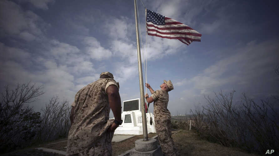 U.S. Marines hoist the U.S. flag on the summit of Mount Suribachi, near the site of a ceremony commemorating the 70th anniversary of the Battle of Iwo Jima, now known as Ioto, Japan, March 21, 2015.