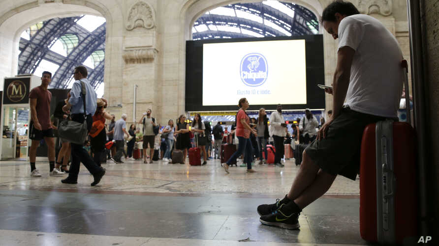 People wait in a railway station, in Milan, Italy, during a general transport strike, June 16, 2017.