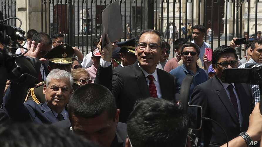 Peru's President Martin Vizcarra holds up a folder as he waves next to next to Prime Minister Cesar Villanueva, left, as they leave the government palace for Congress where he plans to urge legislators to declare an emergency at the attorney general'