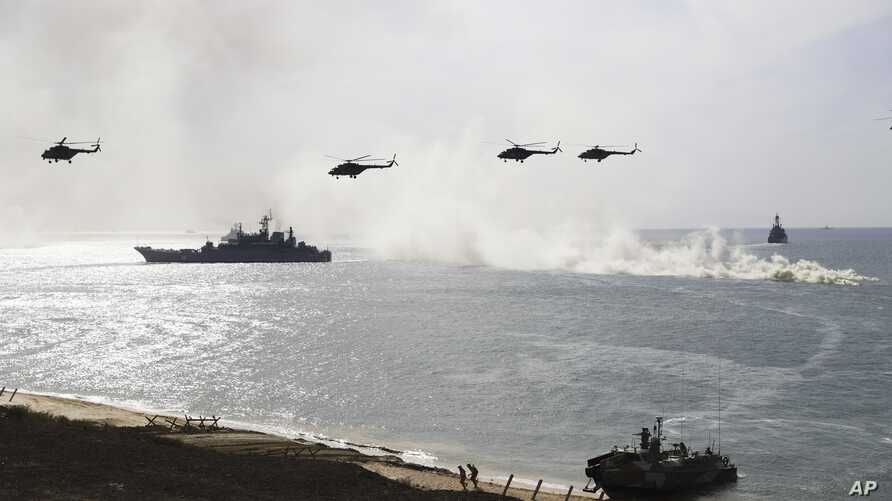 Russian navy ships and helicopters take a part in a landing operation during military drills at Crimea's Black Sea coast, Sept. 9, 2016.