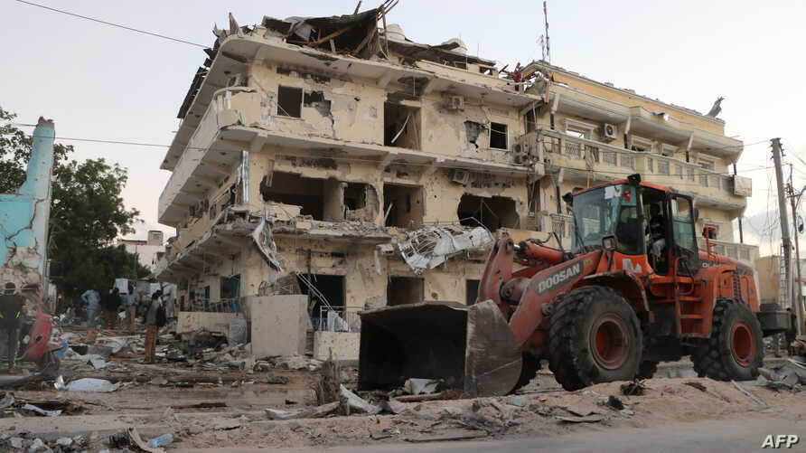 FILE - A backhoe loader clean the street outside the Maka Al-Mukarama hotel in the Somalia capital, Mogadishu on March 1, 2019 after a car bomb exploded, killing at least five people and wounding 25 others.
