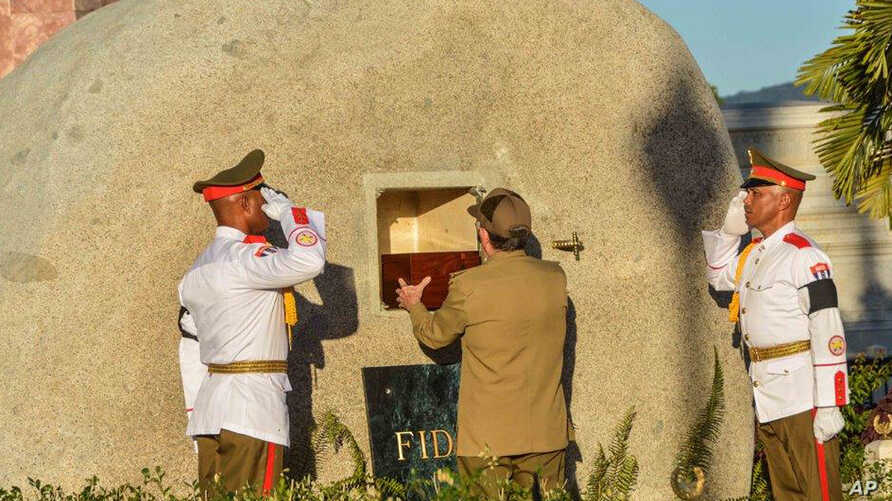 Cuba's President Raul Castro places the ashes of his older brother Fidel Castro into a niche in his tomb, a simple, grey, round stone about 15 feet high at the Santa Ifigenia cemetery in Santiago, Dec.4, 2016.
