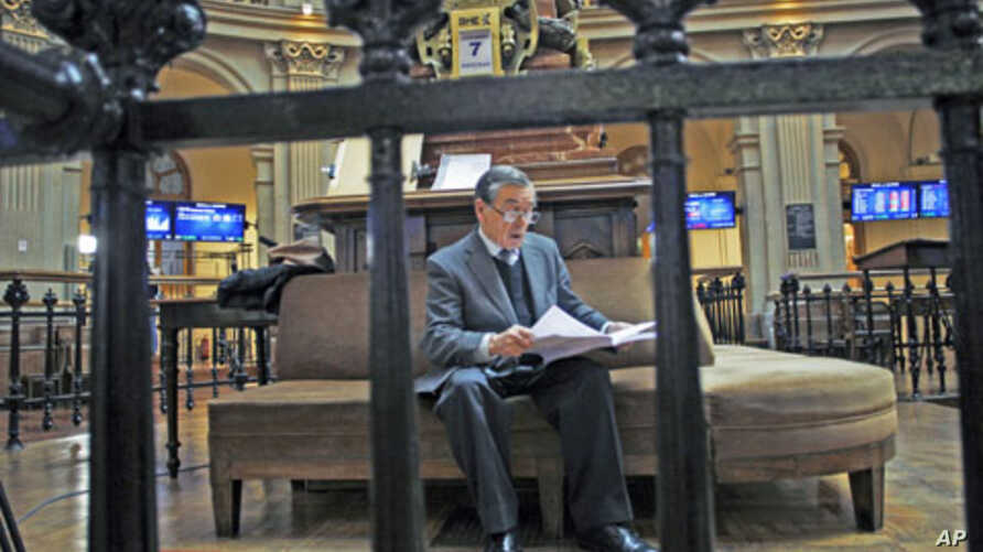 A trader reads at Madrid's bourse as euro gave up gains on comments from a senior German official who dampened optimism that European leaders will take decisive steps to contain the region's debt crisis at this week's summit, in Madrid, Spain, Decemb