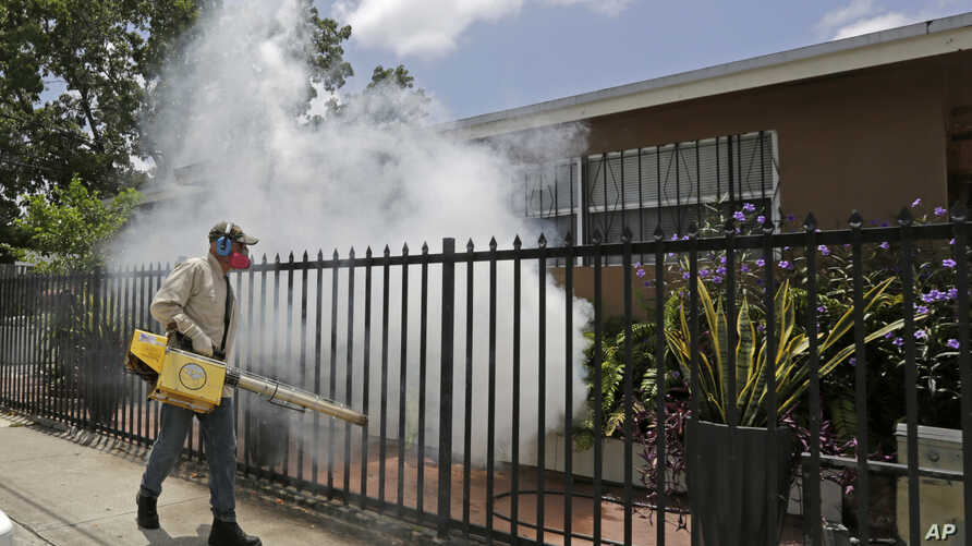 A Miami-Dade County mosquito control worker sprays around a home in the Wynwood area of Miami on Aug. 1, 2016.