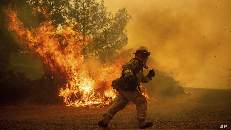 A firefighter runs while trying to save a home as a wildfire tears through Lakeport, Calif., Tuesday, July 31, 2018.